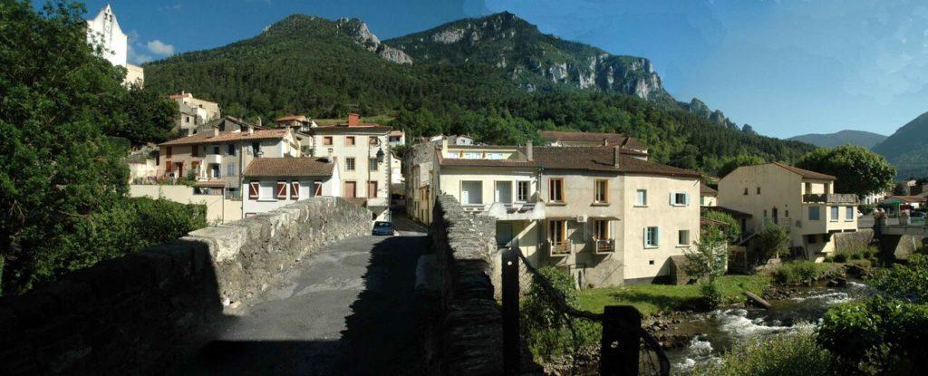 Byen med kirke, romersk bro, bjerge i baggrunden