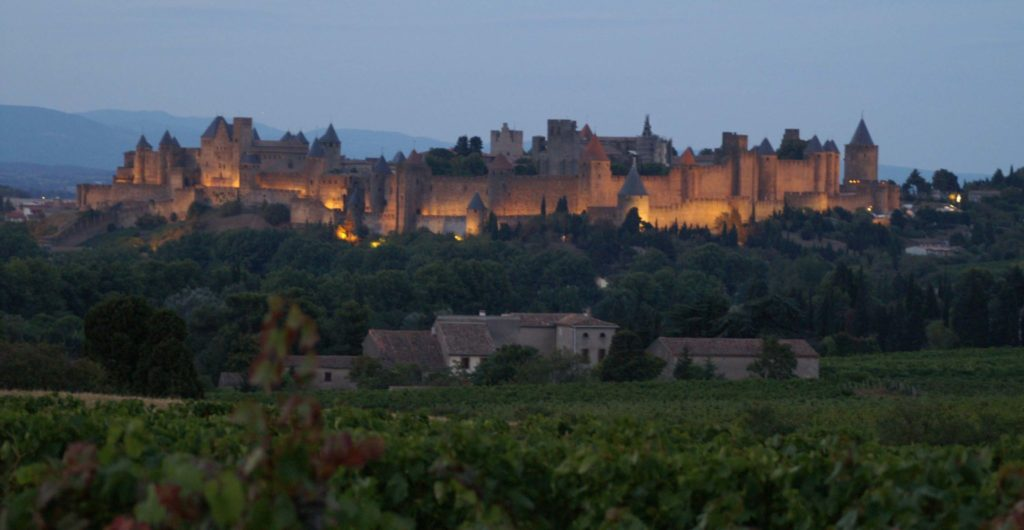 Middelalderbyen Carcassonne i aftenrøde. Der er lys på byen