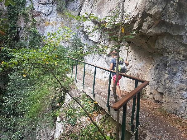 En mand går på gangbro på klippevæggen i en kløft