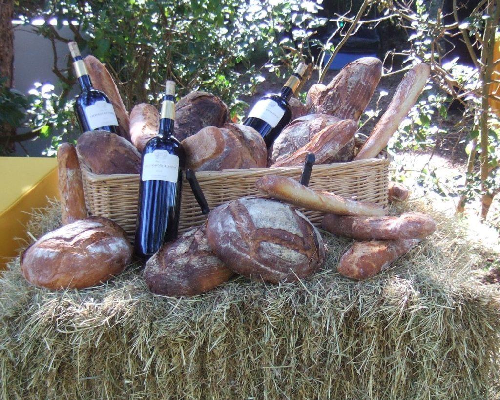 brød og vin står på en halmballe